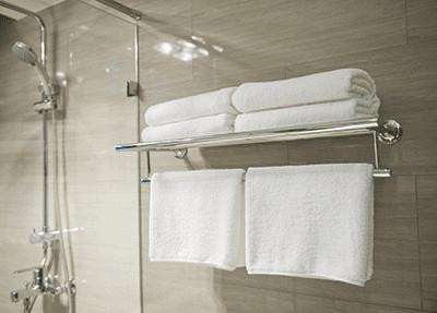 White towels on towel hanger shelf in bathroom