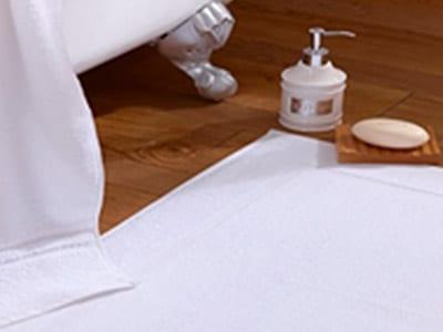 White towel, white bathmat, bar soap, and soap dispenser