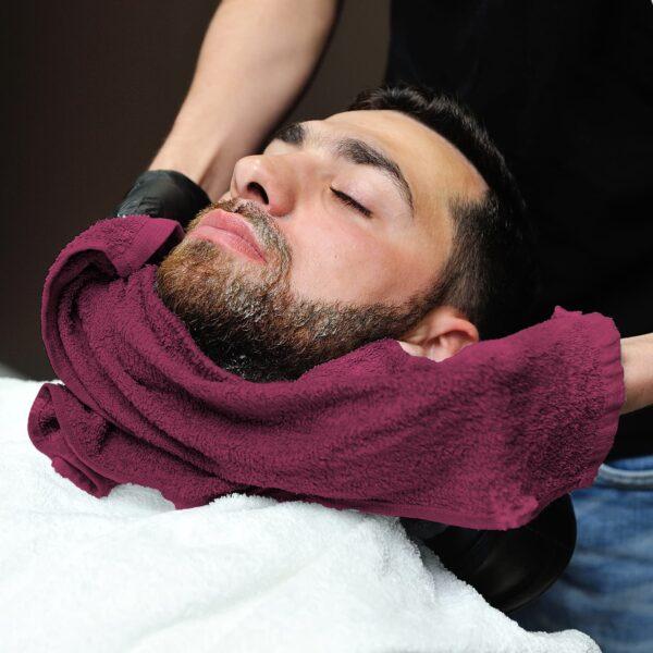 Barber dries customer's beard with burgundy salon towel