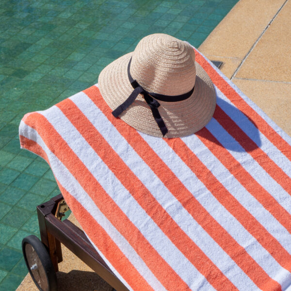 Orange Cabana Pool Towel on poolside chair