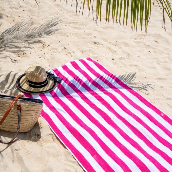 Pink Cabana Beach Towel on sandy beach
