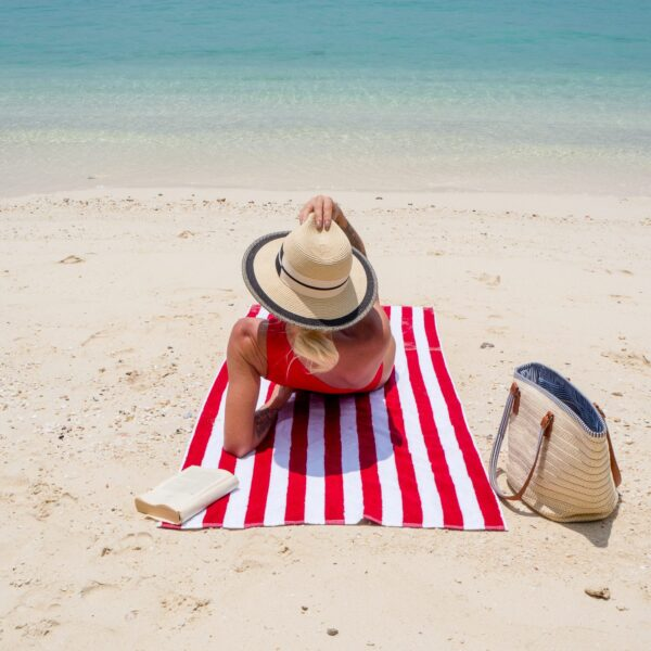 Woman laying on Red Cabana Beach Towel at the beach