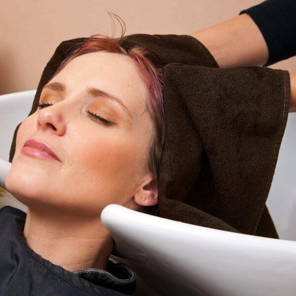 Hair stylist dries customer's hair with chocolate salon towel