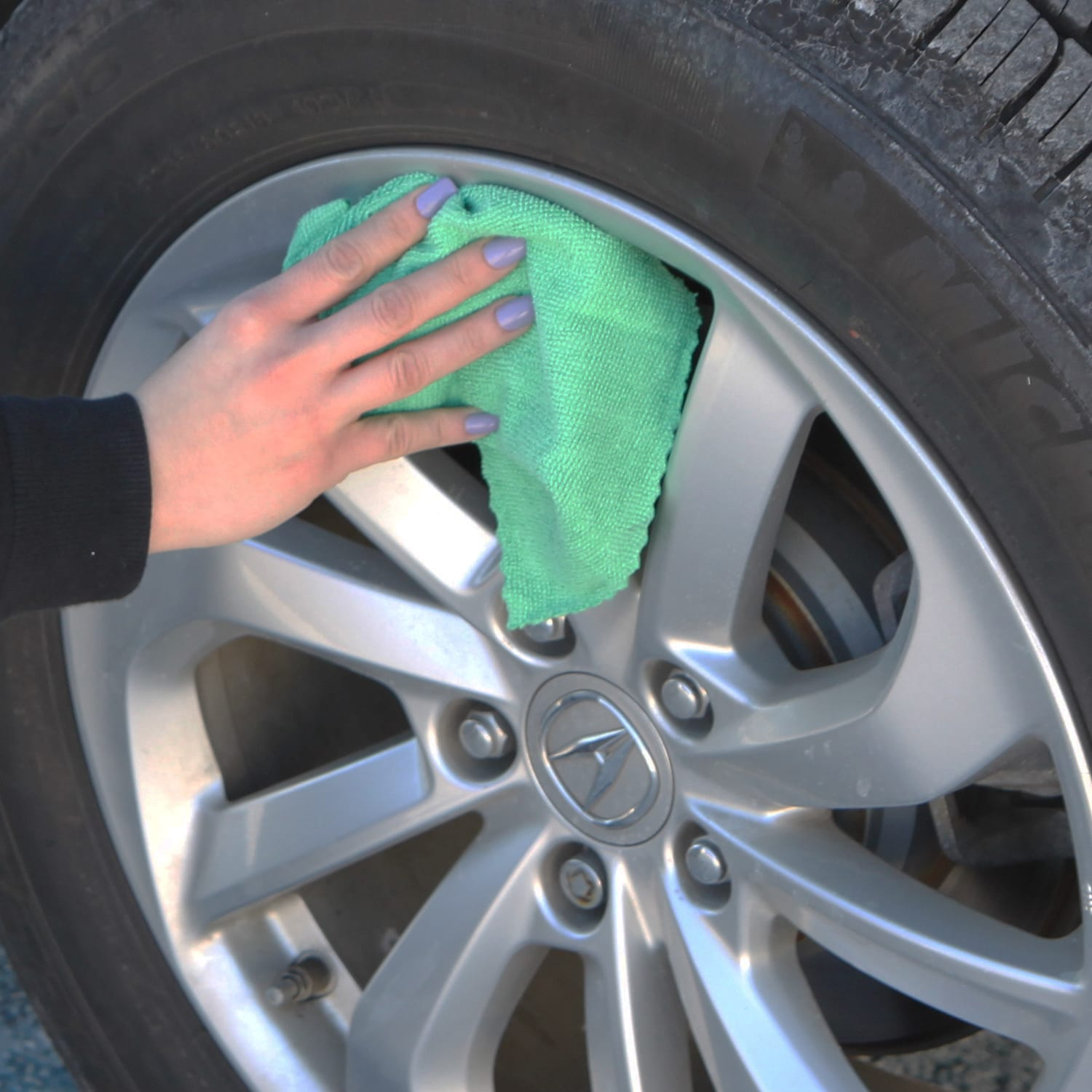Woman cleaning wheel hubcap with Green SmartRags