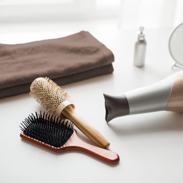 Hairbrush, hair dryer, and brown wash cloths on bathroom counter