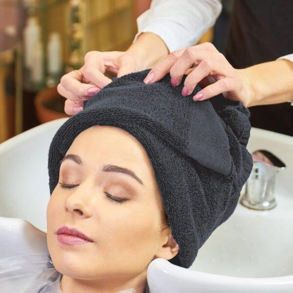 Hair stylist wraps customer's hair in grey salon towel