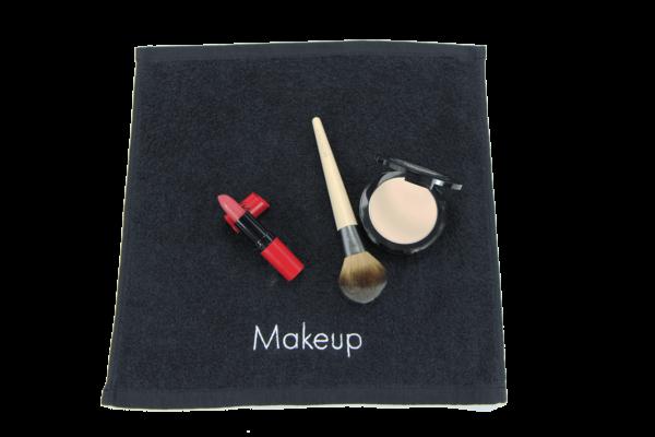 Lipstick, makeup brush, and makeup powder on Makeup Towel