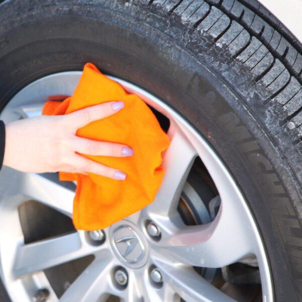 Woman using orange Huck Towel to wipe down wheel hubcap