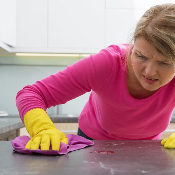 Purple Microfiber Cloth used by woman to wipe off a mess on the kitchen counter