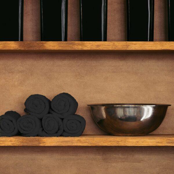 Black rolled up towels on shelf