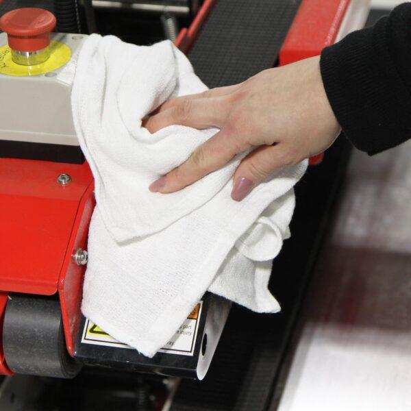 Woman using white Huck Towel to wipe down machinery