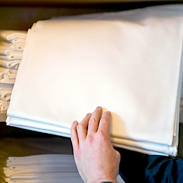 Person grabbing folded white linen sheet from closet