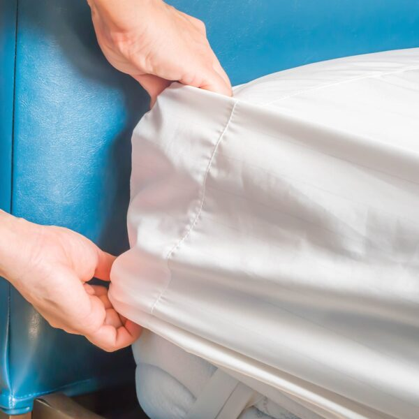 Person inserting white linen fitted sheet cover over mattress