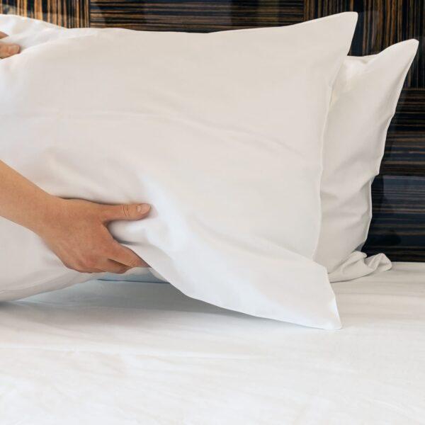 Housekeeping holding white linen pillow