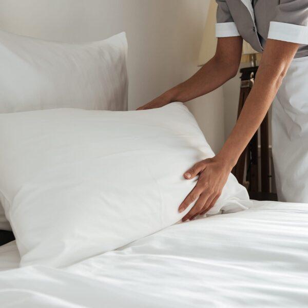 Housekeeper fluffing white linen pillow