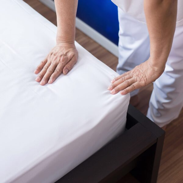 Housekeeping making white linen bed