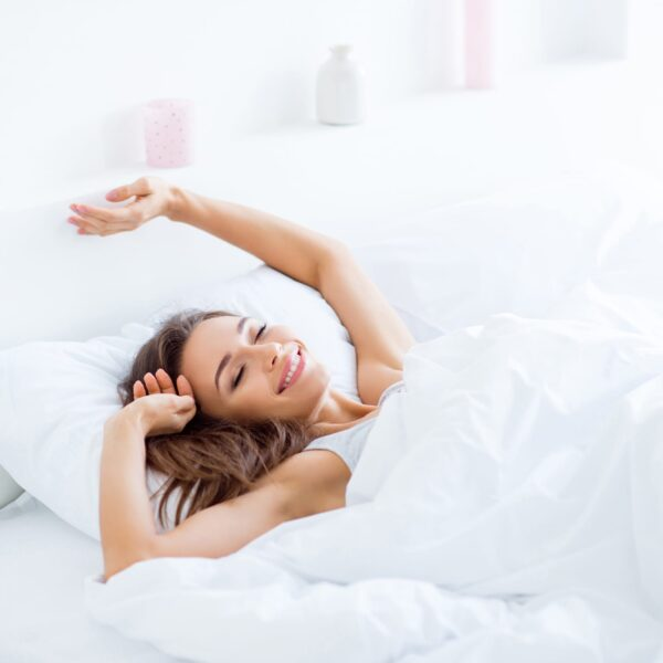 Woman laying in white linen bed