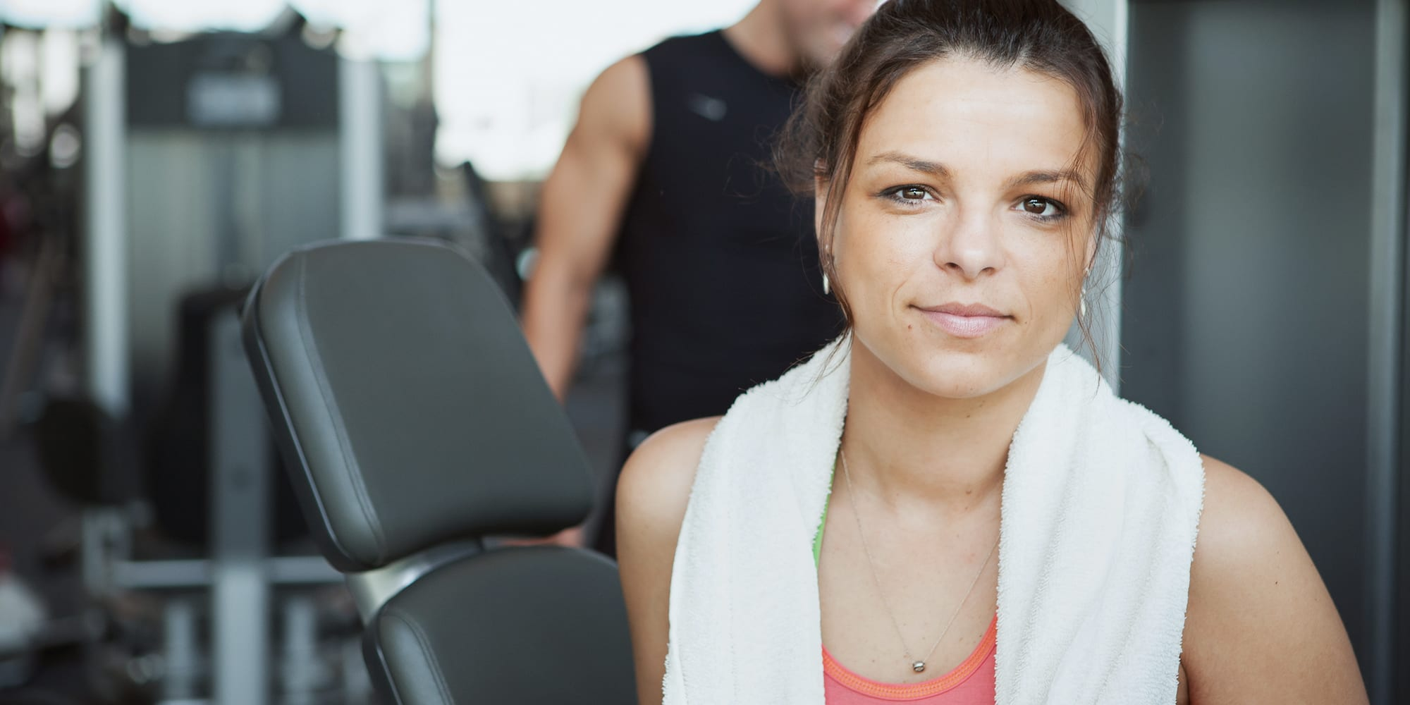 Woman at gym with Monarch Towel draped over her neck