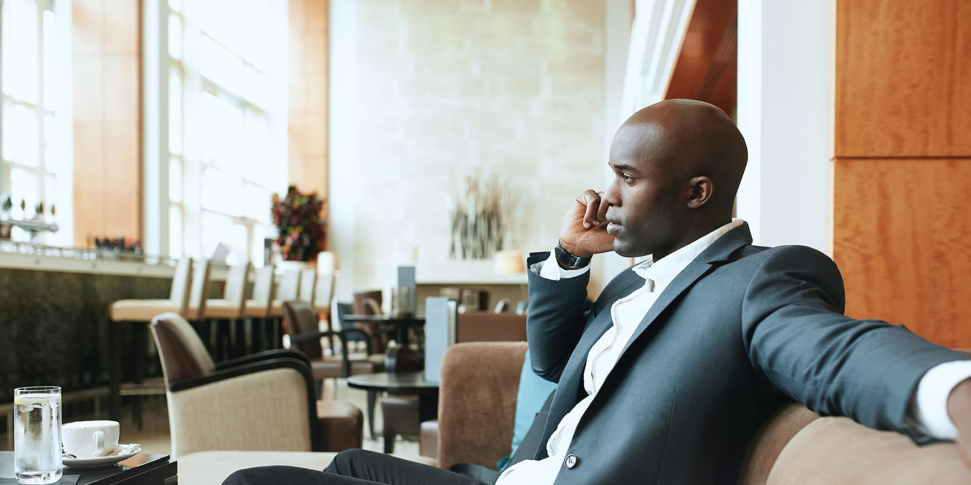 Young man in a suit on the phone at a restaurant