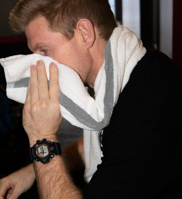 Man wipes sweaty face with Gym Towel with Grey Stripes