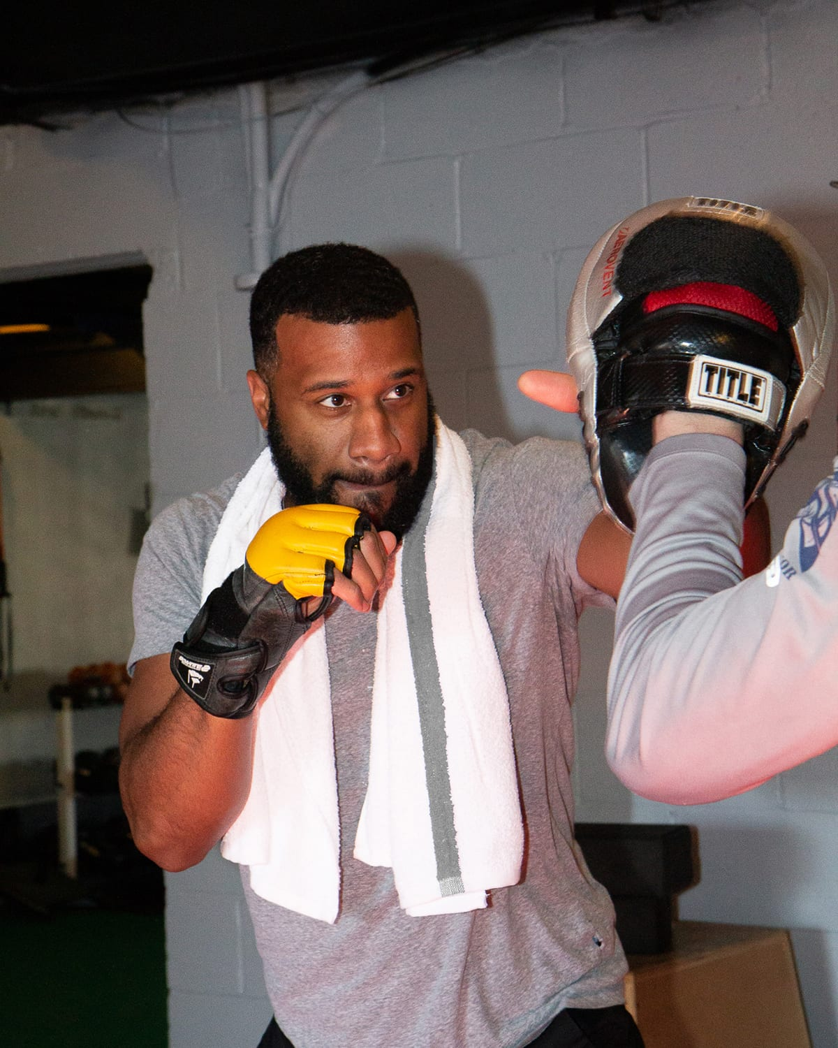 Man boxing with White Bath Towel with Grey Stripe around shoulder at gym