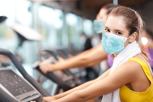 Girl wearing PPE mask on exercise bike