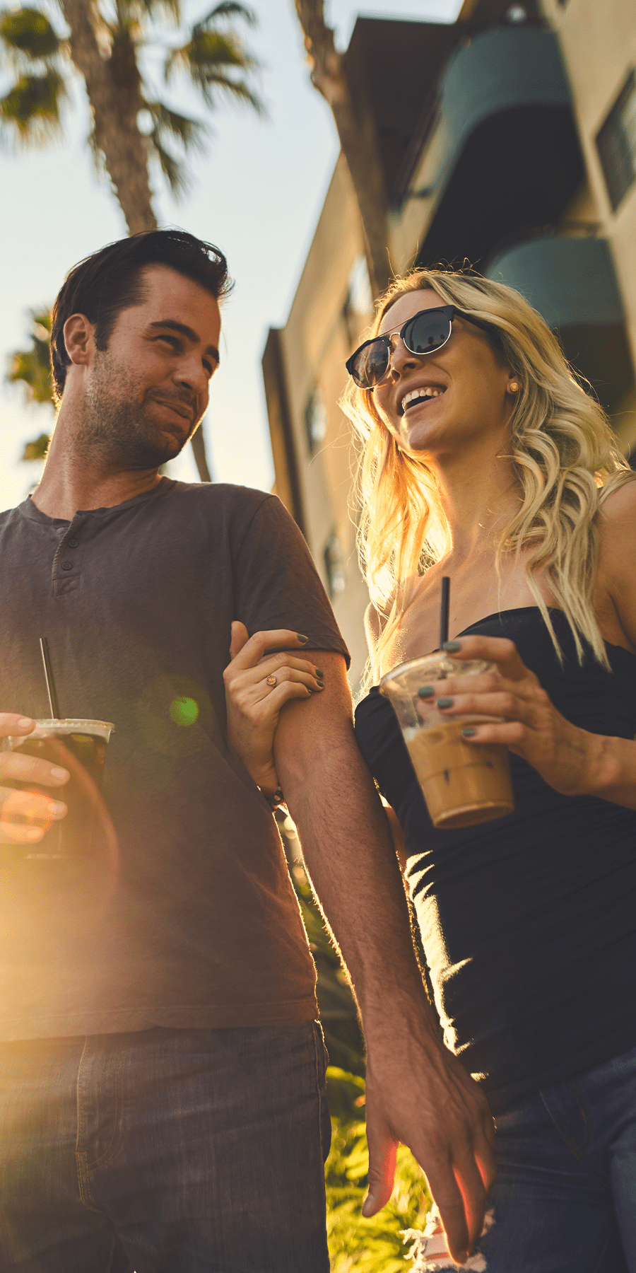 Couple holding iced beverages walking arms linked around the city