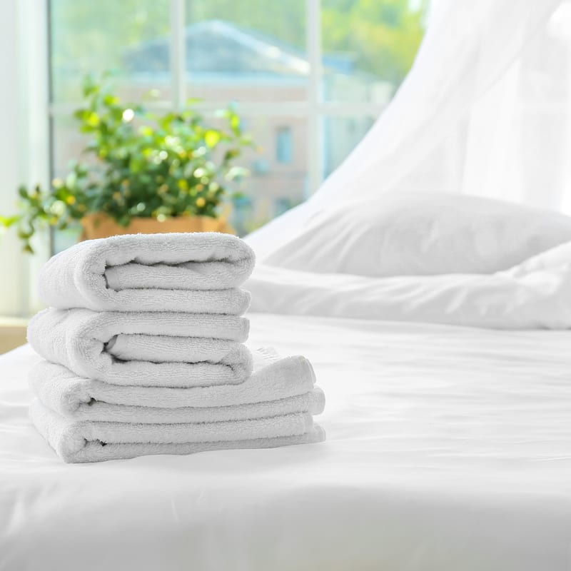 Towels folded and stacked placed on bed