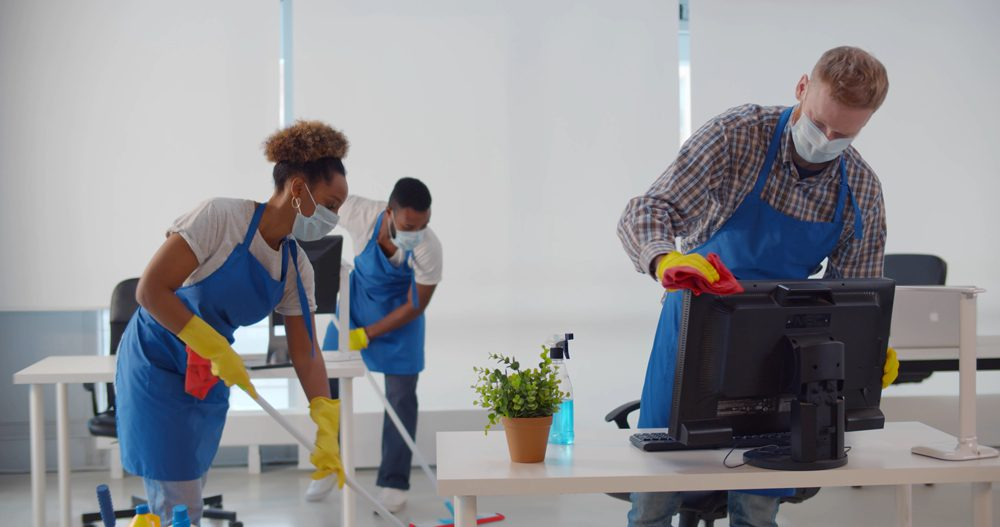 Group of people wearing PPE cleaning an office